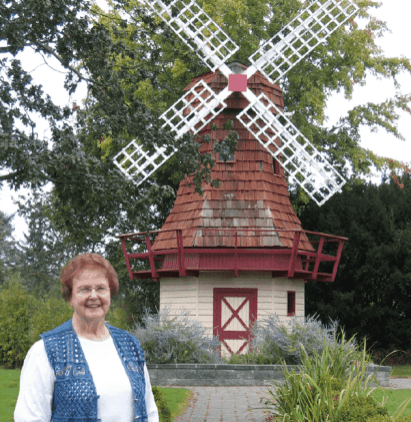 Jan Ellis, an Oak Harbor resident of Dutch heritage, stands in front of the windmill at Holland Gardens Park.