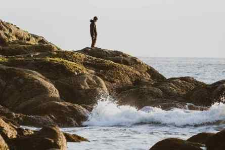 A man hikes over rocks on Rialto Beach.