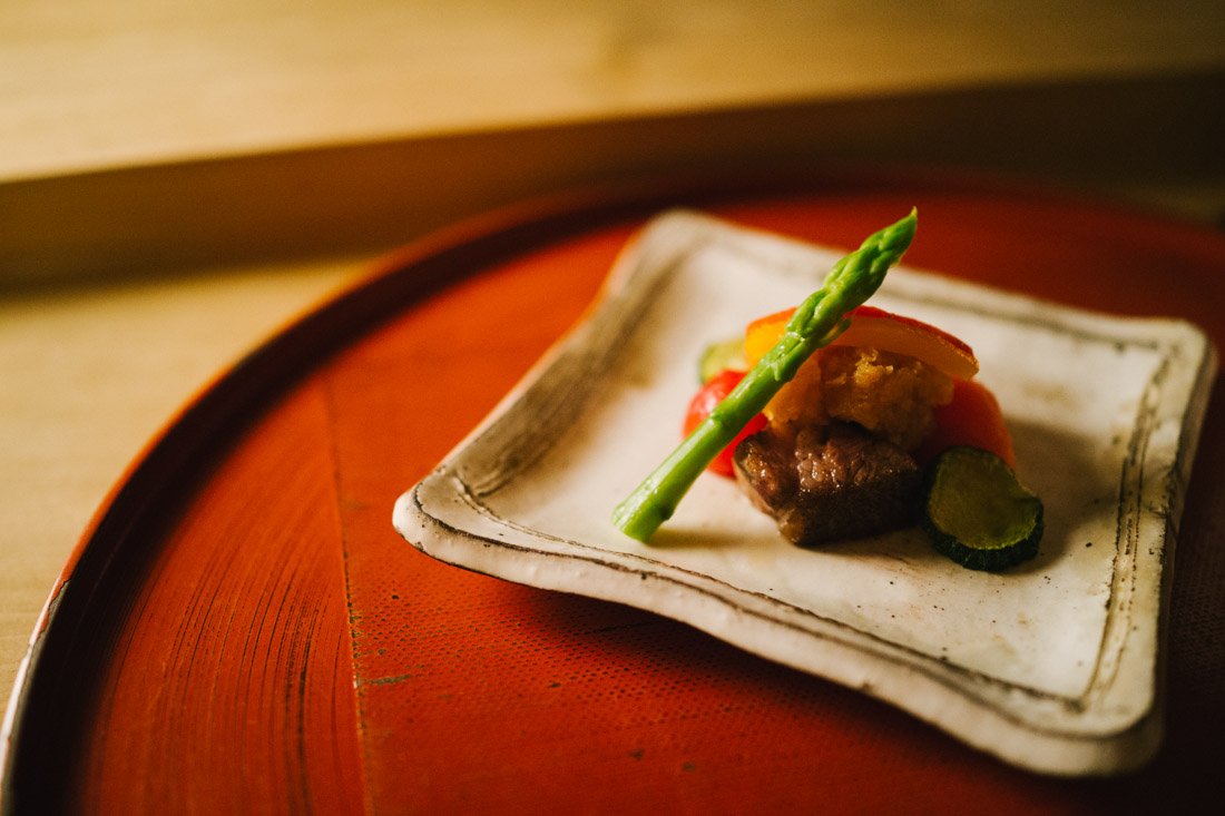 Wagyu beef with cherry tomatoes, bell pepper, white radish and zucchini topped with baby asparagus.