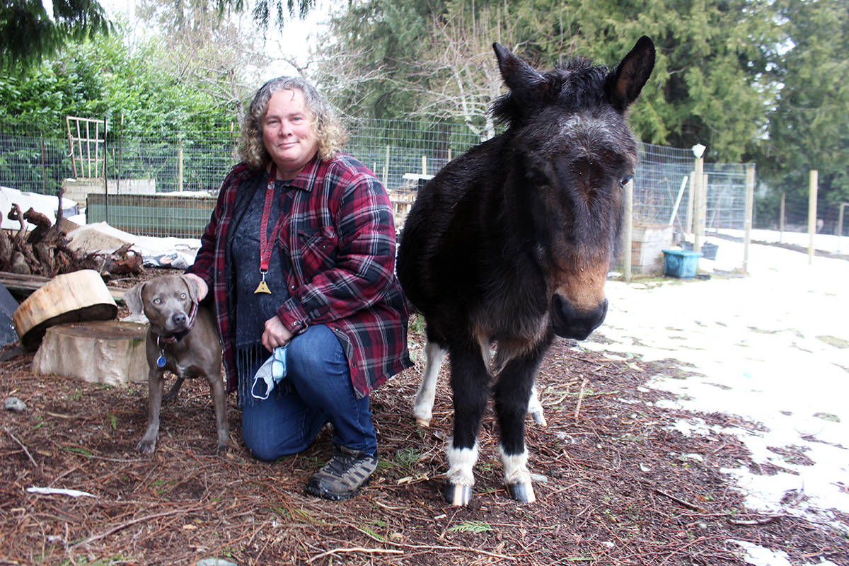 Taliesin the dog and O'Henry the mule are happy to pose for a photo with Zoe MacBean. (Photo by Don Bodger)