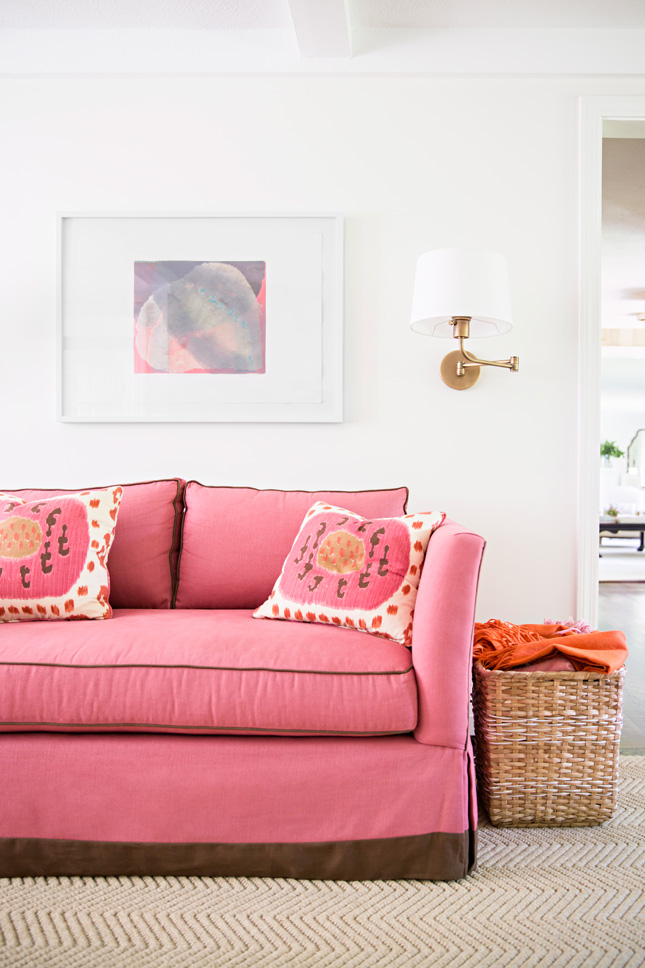 Pretty brass swing-arm sconce in a living room with a pink couch. Design by McGrath II.
