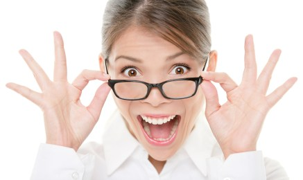 Funny portrait of excited asian woman wearing glasses eyewear. Closeup portrait of young professional business woman making funny face expression isolated on white background. Beautiful young model.