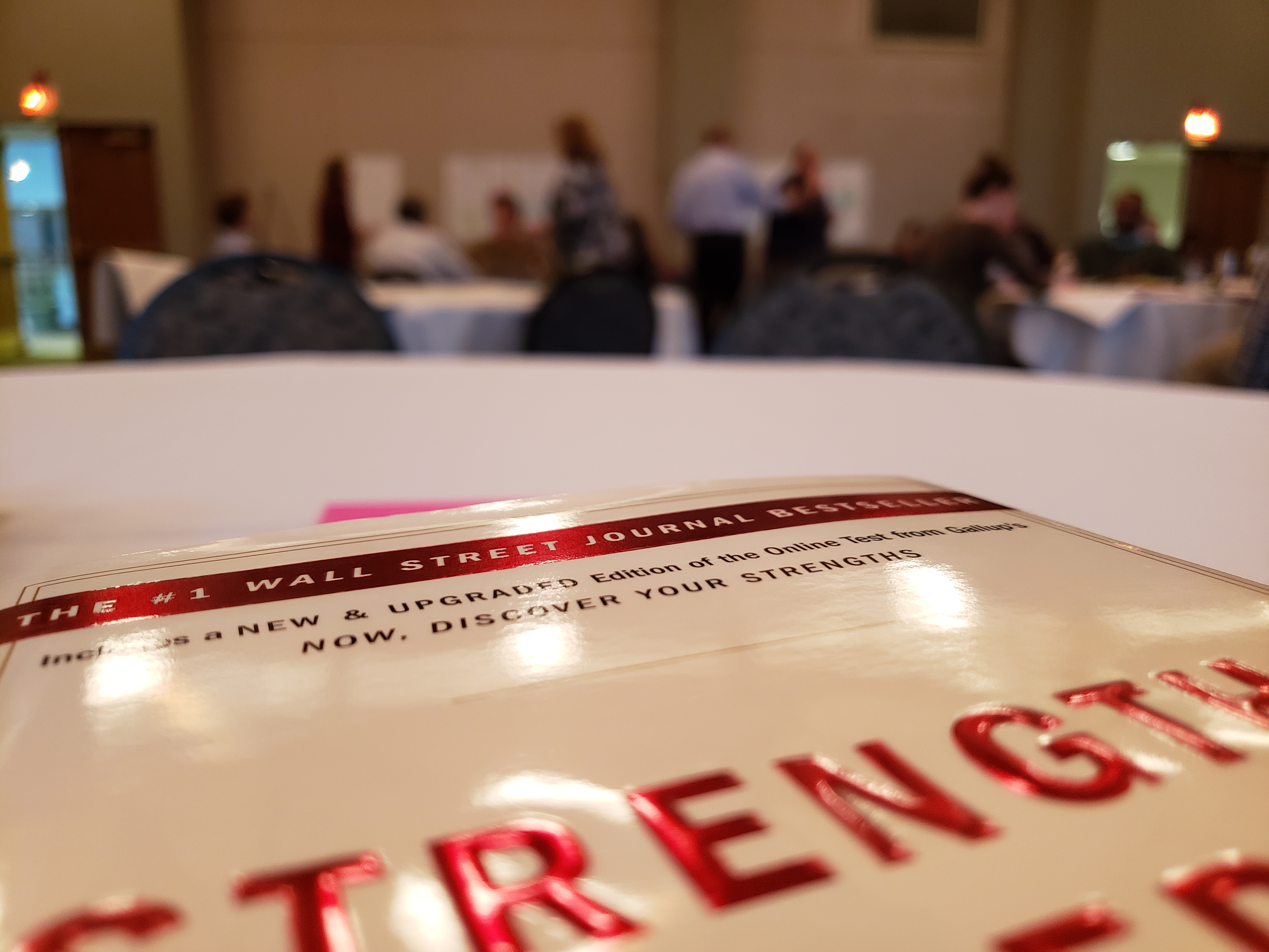 StrengthsFinder book with small groups in the background
