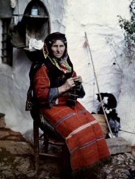 Γυναίκα με παραδοσιακή ελληνική ενδυμασία πλέκει έξω από το σπίτι της στο Αϊβαλί.