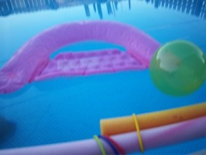 Image of an above ground pool with pink, green, and orange flotation devices, such as a beach ball and a floating lounge chair.