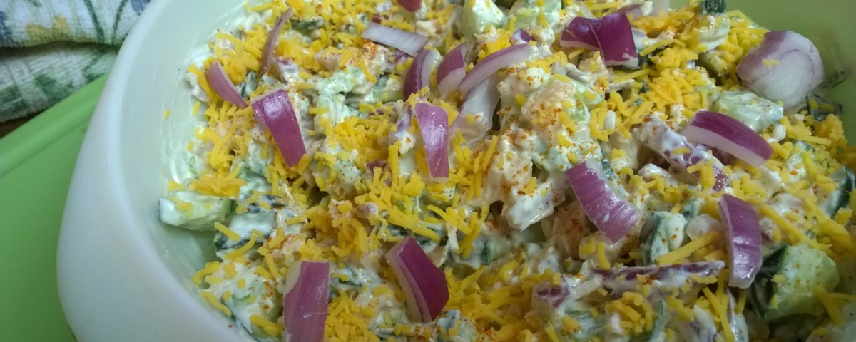 Image of a white bowl filled with a chicken salad containing a variety of vegetables such as green peas, yellow corn, chopped broccoli slaw with grated carrots, mayo, cheese and purple onions on white background