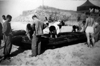 Preparing one of the hated rubber boats for another trip through the surf.