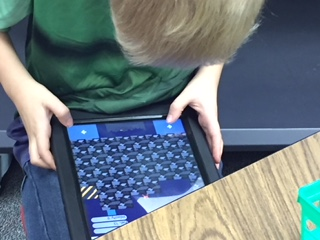 Student on ipad for golden tickets rewards.