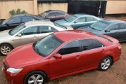 Nigerian youths celebrate the acquisition of new vehicles in Benin