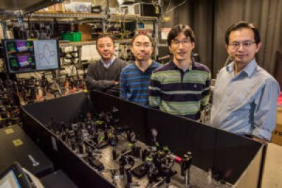 (From left) Berkeley researchers Xiang Zhang, Zi Jing Wong, Jeongmin Kim and Yuan Wang stand next to the optical setup they designed to demonstrate both lasing and anti-lasing in a single device. (Credit: Marilyn Chung/Berkeley Lab)