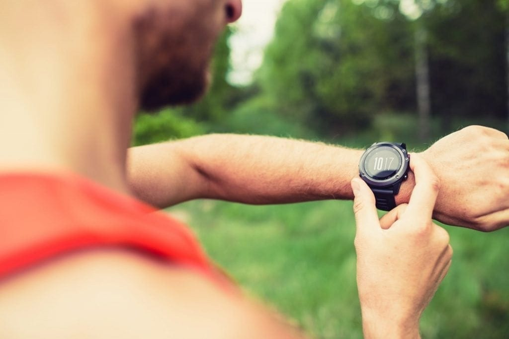 Runner on mountain forest trail checking looking at sportwatch smart watch, cross country runner checking performance, GPS position or heart rate pulse. Sport smartwatch and fitness equipment in use outdoors in nature on summer trail
