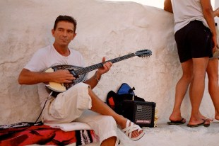 This street performer, however, had a look of practiced ease. He gave his bouzoki, a traditional Greek instrument related to the mandolin, a modern twist with its stereo hookup.