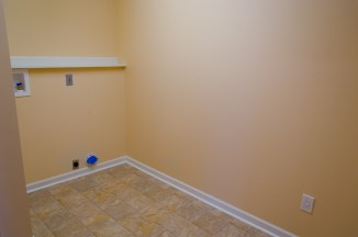 Large laundry area with hookups and plenty of space for a table or ironing board.