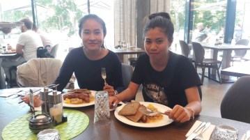 """Ms Moukdala Keomixai and Ms Siliphone Arnousavanh enjoy traditional German """"Bratwurst [sausage] and Sauerkraut"""" in the company restaurant of BHS Corrugated"""
