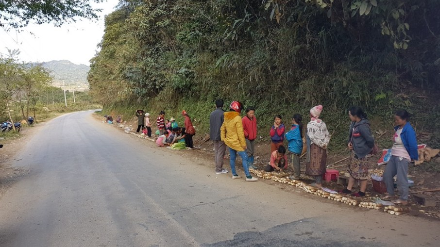 Khamsee and Bounphay bargain with the girls and women on the side of the street to get the best price for the bamboo shoots.