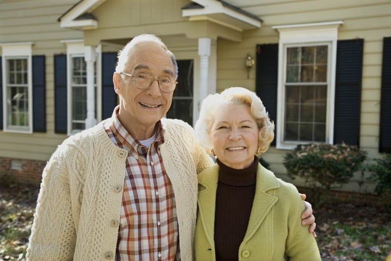 Portrait of senior couple in front of their home