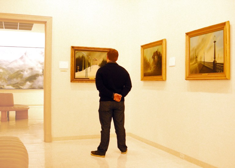 A museum patron looks at works by Felix Kelly