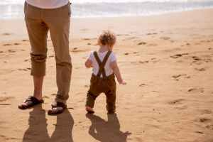 toddler walking on sandy beach with faceless father