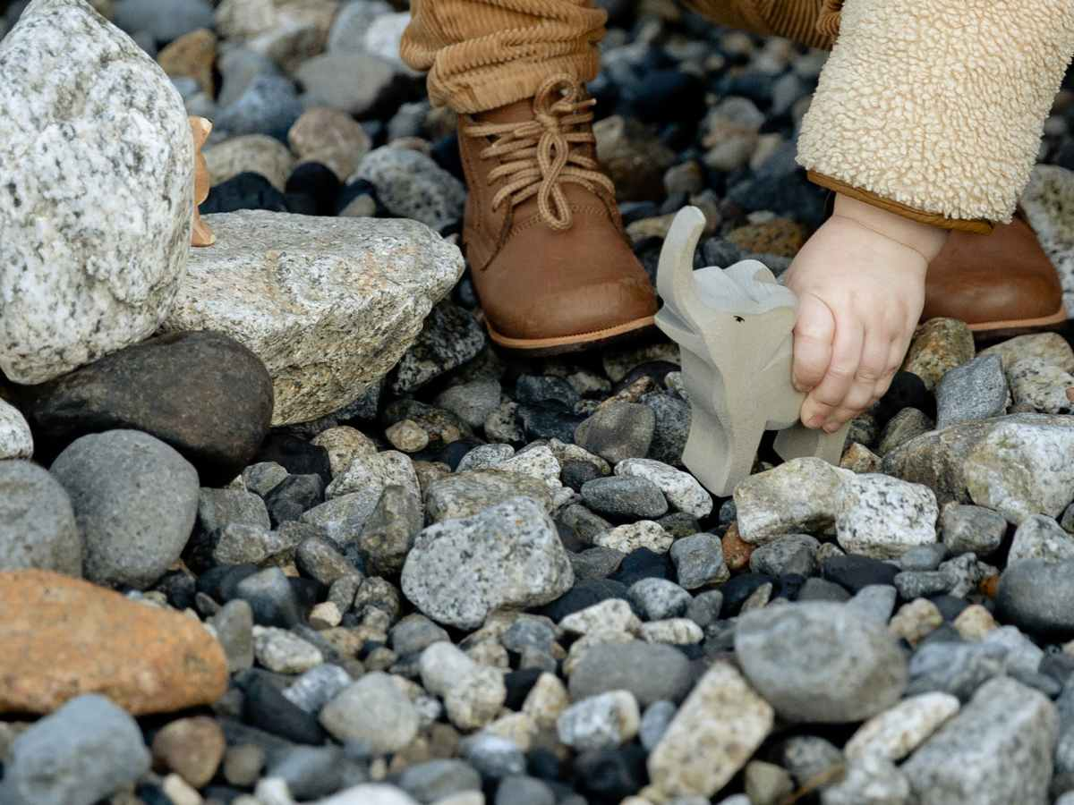 crop anonymous kid playing with toy on stones of shore