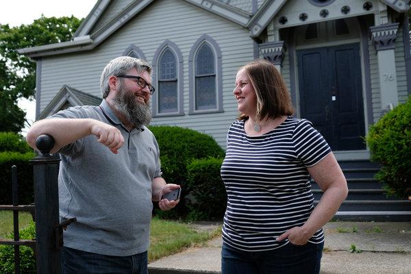 """布恩(左)和卡萝·谢里登在马萨诸塞州霍利奥克的家里。他们家被列为《精灵宝可梦Go》的""""道馆""""之一。数天来,外面一直有玩家聚集。"""