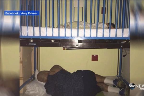 美国一名身材魁梧父亲,在医院蜷缩著身体睡在婴儿床下的照片,感动无数网民。(ABC新闻视频截图)