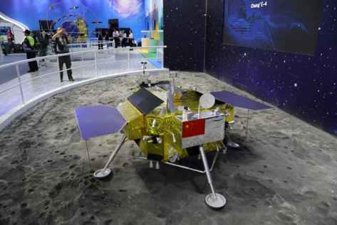 man takes a photo of Chang'e 4 probe moon lander model at an exhibition