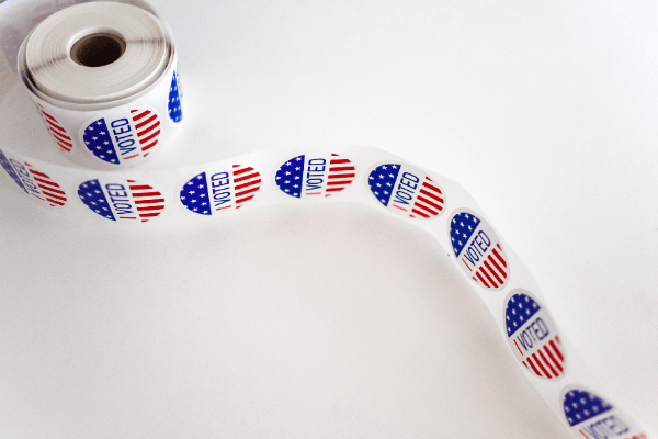 "picture of a roll of red and white ""I VOTED"" stickers"