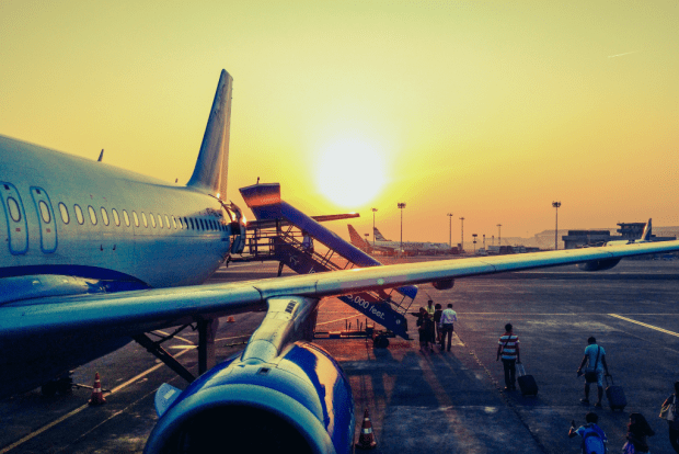 photo shows airplane at an airport at sunset