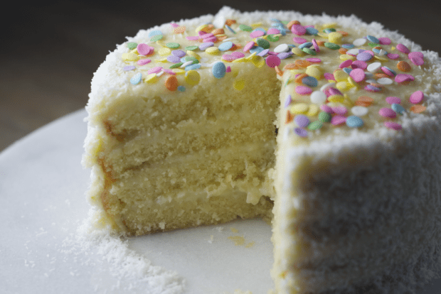 photo shows a yellow cake with rainbow sprinkles with one piece gone