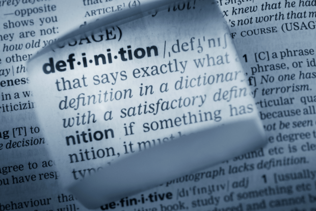 "photo shows a magnified excerpt of a dictionary entry for the word ""definition"""