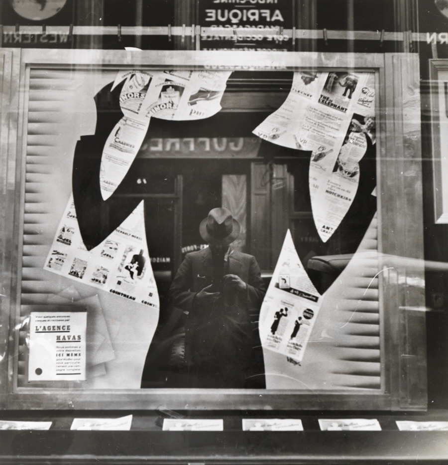 Photographer's reflection in a cut-out silhouette in a window.Photograph by Maynard Owen Williams, National Geographic