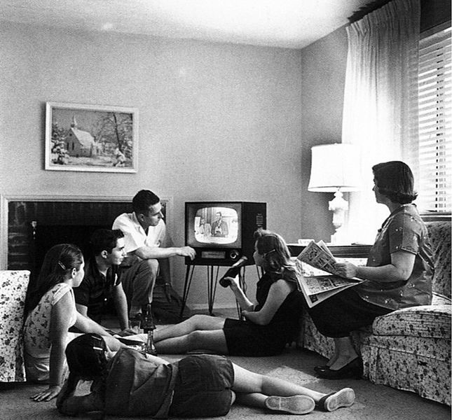 Black and white, 1950s American family of four, sipping Coke, sitting in the livingroom gathered around the small black and white television.