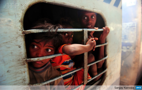 afp-photo:INDIA, Allahabad : Young Indian commuters sit inside a crowded train compartment at Allahabad junction in Allahabad on June 22, 2013. AFP PHOTO / SANJAY KANOJIA