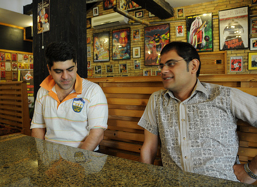 Rafay Alam (left, with popped collar) and Raza Rumi (right, in block print) hang out in a Muslim burger and ice cream joint with their Muslim shirts. In the background: very Muslim gory pop art on the walls.