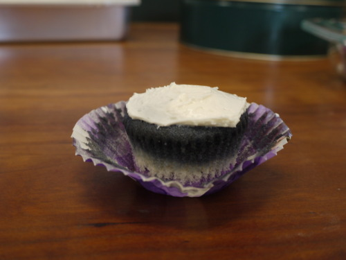 Image description: A cupcake with the purple, light purple, and white wrapper pulled back to expose the cake. The cupcake has the stripes of the asexual flag: purple on the bottom, then white, then gray, then black, with white icing on top.