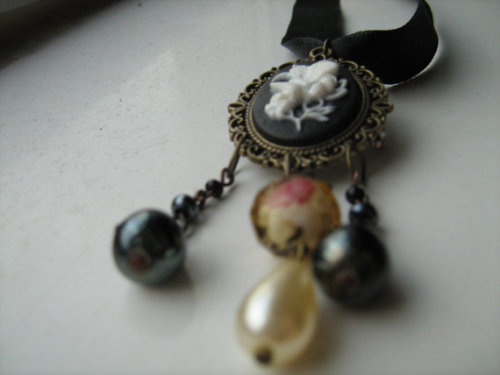 25 and a half inch / 65 centimetre black satin ribbon TIE CLOSURE Victorian style choker with brass framed black and white floral cameo in resin, glass and acrylic beads, ceramic lustre and glass pearl drops, and a rose cake cut glass crystal bead. Cameo features a brooch pin back: ribbon can be removed so cameo can also be used as a brooch.This one of a kind, dual-function necklace is perfect for flower-lovers of all ages, goths, steampunks, and those who just really like to dress up an outfit. As a choker it is charming and comfortable, the satin ribbon adjustable to tie for almost any neck size; as a brooch it is unusual and eye-catching and looks smashing with a smoking jacket or blazer.