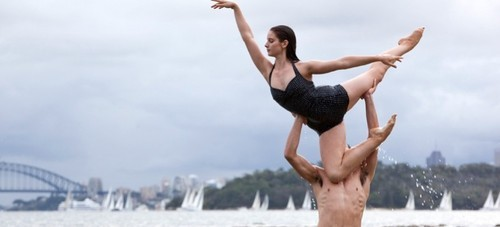 White teens practice ballet on the beach, the Sydney Harbour Bridge in the background.