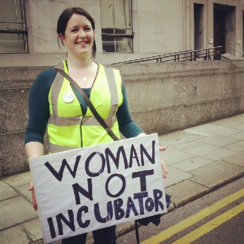 "Woman carrying sign saying ""Woman, not Incubator"""