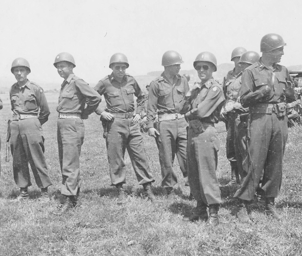 62a. Enlargement of photo No.62. Cham Germany Parade Day, 10 May to 11 July 1945. L to R;. 1st Lt. Thomas J. McLaughlin, B Battery; Captain Daniel E. Brewer, B Battery; 1st Lt. Bernard T. Kaylor, jr., C Battery; 1st Lt. Frank J. Mauger, HQ Battery; PFC M. M. Matta, A Battery; 1st Lt. Jacob W. Shinaberry, B Battery; 1st Ltr. John P. Perferri, C Battery; 1st Lt. Thomas B. Marriott, jr., B Battery