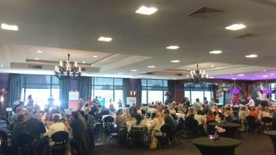 Een volle zaal met mensen aan tafels tijdens het congres