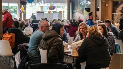 Mensen binnen, met hun jas aan, die met elkaar praten, koffie drinken en gebak eten