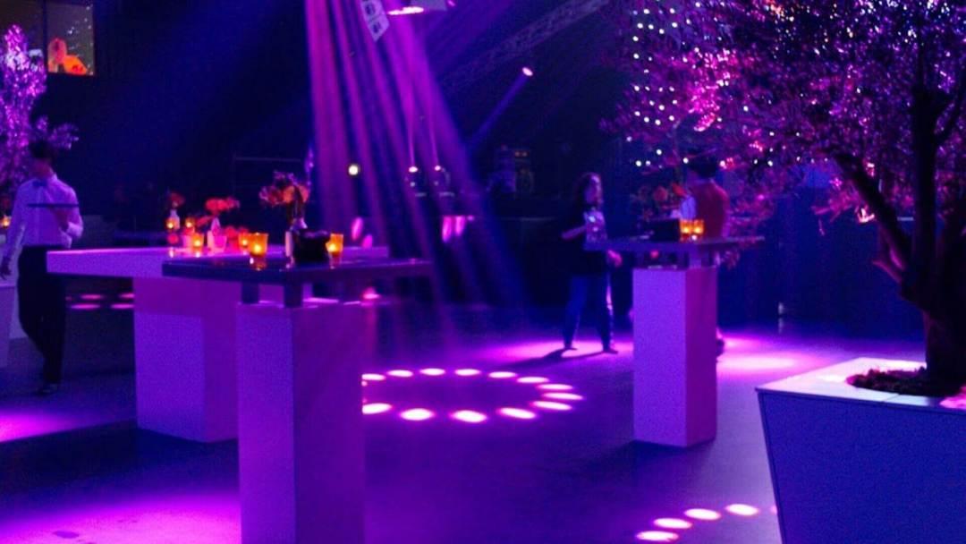 Verschillende statafels met bloemstukken erop als aankleding bij een bedrijfsfeest. Roze en paarse sfeerverlichting erboven