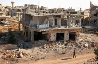 A rebel fighter walks past damaged buildings in a rebel-held part of the southern city of Deraa, Syria.