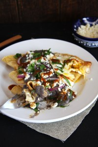 Classic Mexican Enfrijoladas- tortillas bathed in a flavorful black bean sauce and topped with cheese, red onion, cilantro, salsa and a fried egg. #mexican