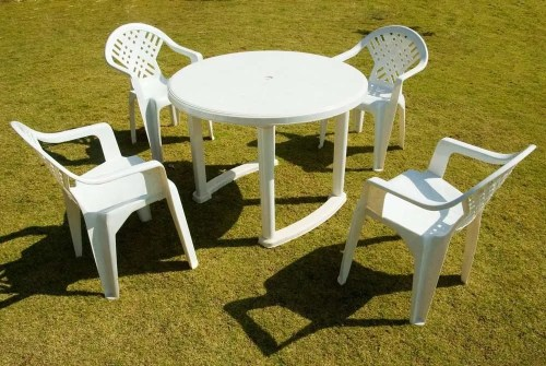 Four white plastic chairs with a round white table
