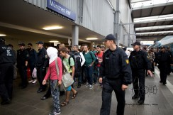 Another group of migrants is led through Munich central station to be reigestered.
