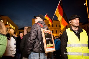 """pegida 121015 2 - Man with """"Der Spiegel"""" cover page stands amongst the PEGIDA crowd."""
