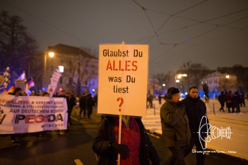 """Do you believe in everything you read?""-sign carried by Birgit Weißmann - whilst cussing at photographers to be ""Zecken"""