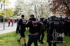 Neo-nazi wearing Thor Steinar covers his face to protect himself from tear-gas launched.