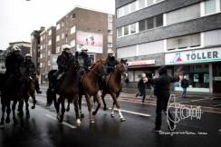 Police galop towards counter-protestor.
